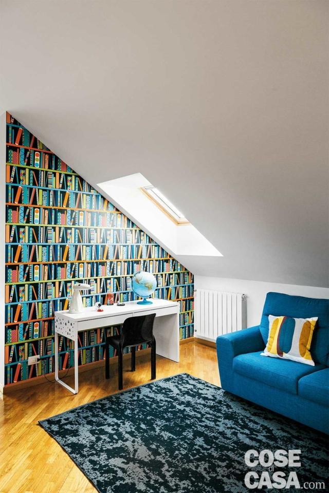 Nella zona studio, lo scrittoio è illuminato in modo diretto dal lucernario. La carta da parati riproduce in modo stilizzato gli scaffali di una libreria.