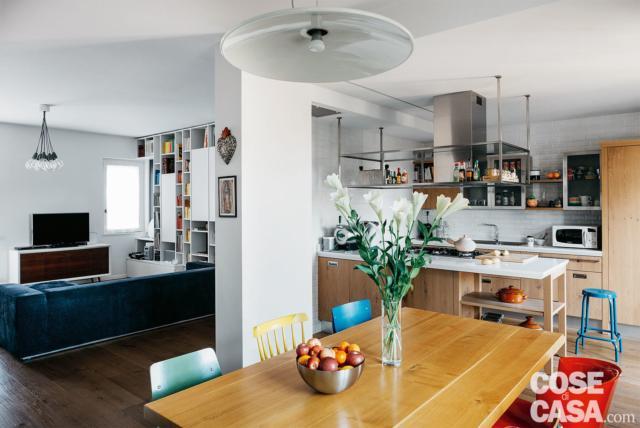 La zona pranzo è definita dal pilastro portante alle spalle. La sospensione ad altezza regolabile che illumina il piano in legno del tavolo è anni '60.