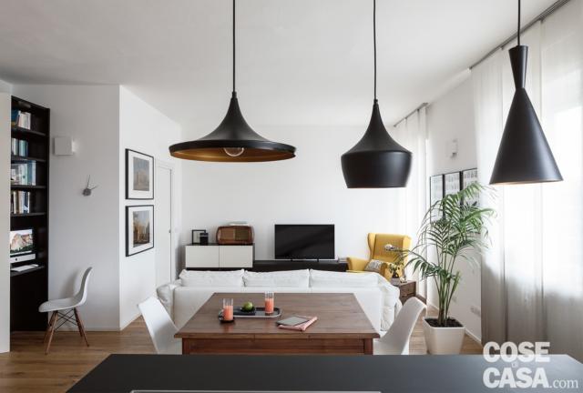 tavolo da pranzo, lampade nere di design e zona conversazione open space