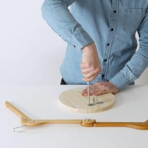 Se non avete la base rotonda con le misure richieste, tagliatela con il seghetto alternativo da un'asse più grande. Con le viti da legno fissate le due lastrine piegate sulla base.