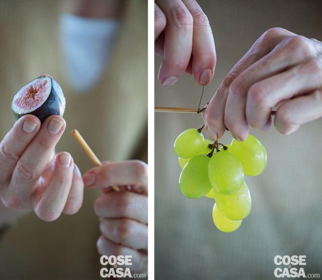 7. Preparare le frutta: tagliare a metà i fichi e suddividere il grappolo d'uva in racimoli. Infilare ogni mezzo fico su uno stecchino. Legare ogni racimolo a uno stecchino arrotolandogli intorno il filo di ferro. Infilare gli stecchini nella spugna, recidendoli all'altezza necessaria per lasciare intravvedere solo la frutta tra i fiori. Ricordarsi di inserire un mezzo fico e un racimolo nella parte alta, vicino alla prima rosa.