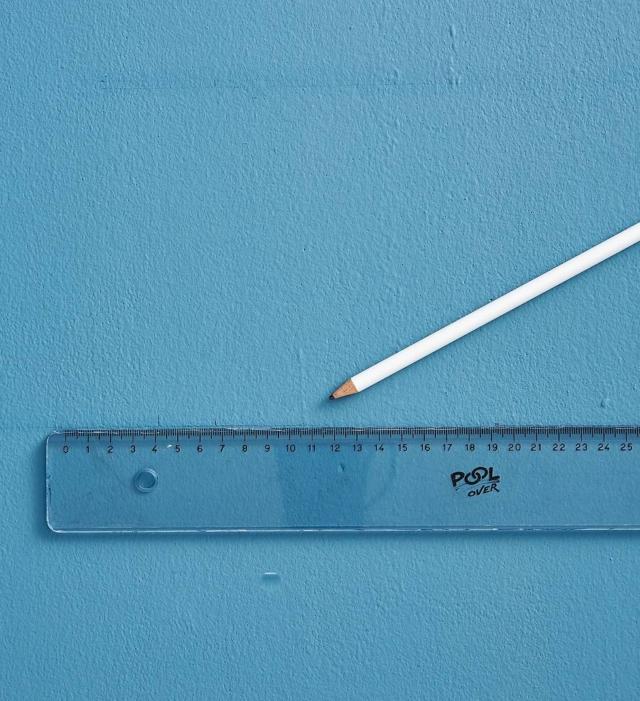 Con matita e righello disegnare sul muro, con tratto leggerissimo, la sagoma di un rettangolo verticale, pari all'ingombro dell'albero da realizzare. Tracciare una linea verticale sulla mezzeria della base fino a incontrare il lato opposto (il punto coincide con il vertice dell'albero). Disegnare tre linee orizzontali equidistanti, tali da dividere il rettangolo in 4 parti uguali.