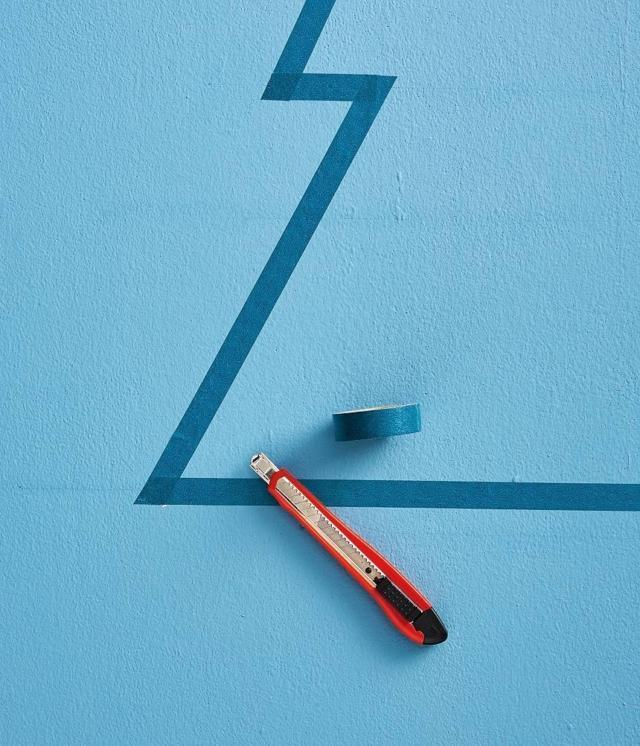 Per definire la sagoma dell'albero, sulla prima linea orizzontale sopra la base, segnare 2 punti all'interno della linea verticale perimetrale a 5 e a 10 cm. Sulla seconda linea orizzontale segnare i 2 punti a 10 e 15 cm. Infine, sulla terza a 15 e 20 cm. Ripetere l'operazione sull'altro lato verticale. Con l'aiuto del righello, a matita, unire tutti i punti su entrambi i lati, per definire il profilo dell'albero. Partendo dal vertice, fissare il washi tape lungo le linee diagonali, poi fissare il nastro sulle linee orizzontali, sagomando gli angoli con il cutter.