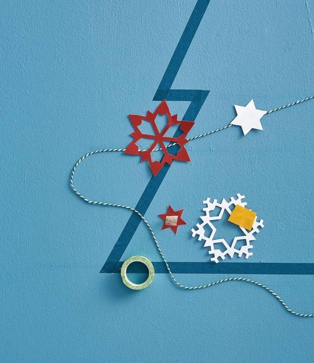 Una volta individuata la composizione giusta, fissare il cordino al muro come fosse un classico festone decorativo, bloccandolo con il washi tape alle estremità ed eventualmente in altri punti per farlo aderire meglio. Si può impreziosire l'albero con piccoli decori di carta sempre a tema natalizio.
