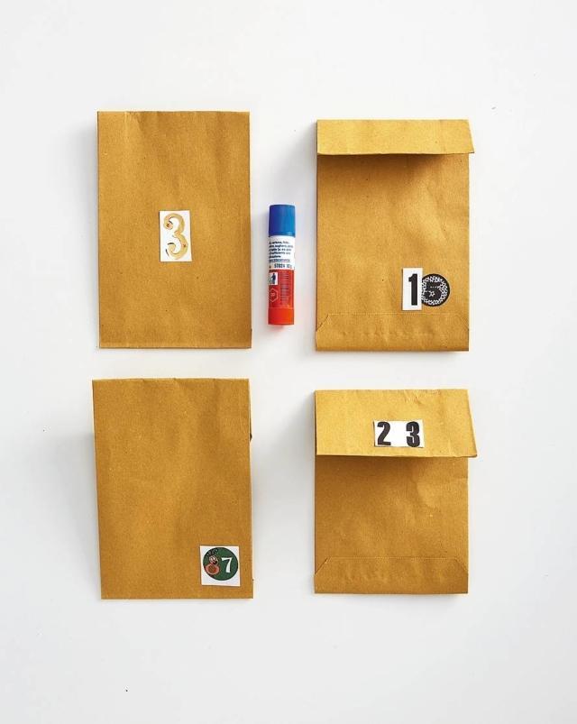 """Con la colla stick, incollare i numeri sui sacchetti, scegliendo la posizione in base al gusto personale. Per variare i formati dei """"pacchetti"""", piegarne la parte superiore, come a formare la linguetta di una busta, per esempio a metà o a 3/4, alternando la posa della cifra sul lato anteriore e posteriore."""