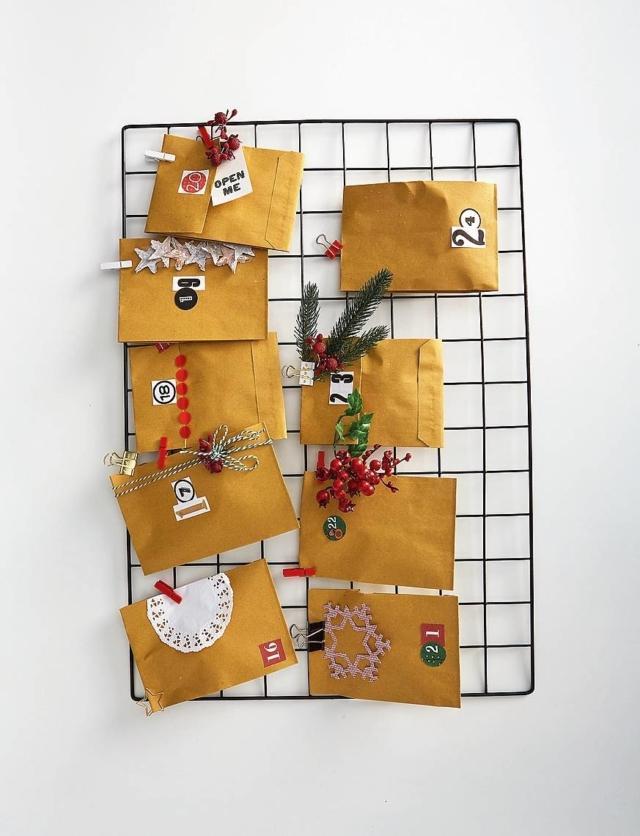 Inserire i regalini all'interno dei singoli sacchetti, chiuderli con graffette, puntine, washi tape, colla e fissarli in sequenza ai due pannelli grigliati di metallo, da appendere al muro, uno sotto l'altro. Agganciare le buste, utilizzando mollette e fermapacchi di vario formato e colore. Per finire, arricchire la composizione con palline e addobbi di Natale che contribuiscono a  creare la giusta atmosfera.