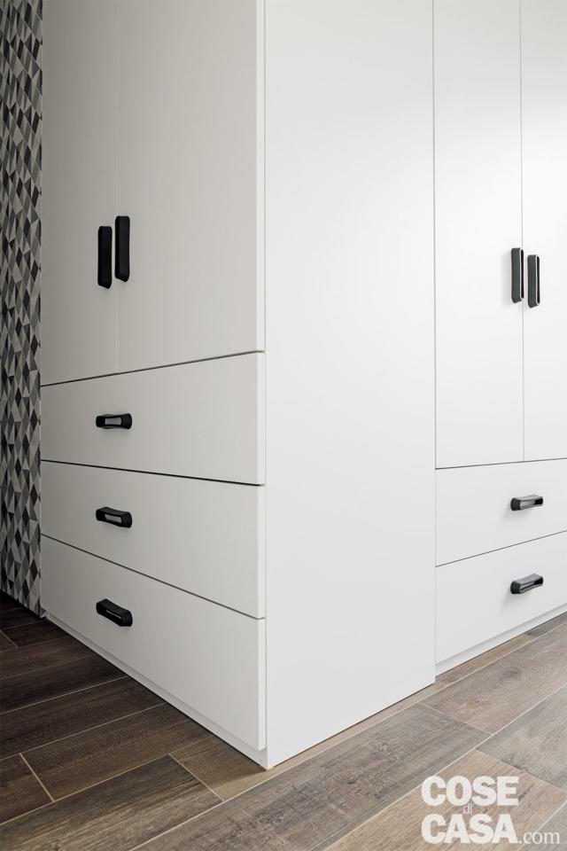 camera matrimoniale, blocco armadi e cassettiere in laccato bianco con sviluppo ad angolo, pavimento in gres effetto legno