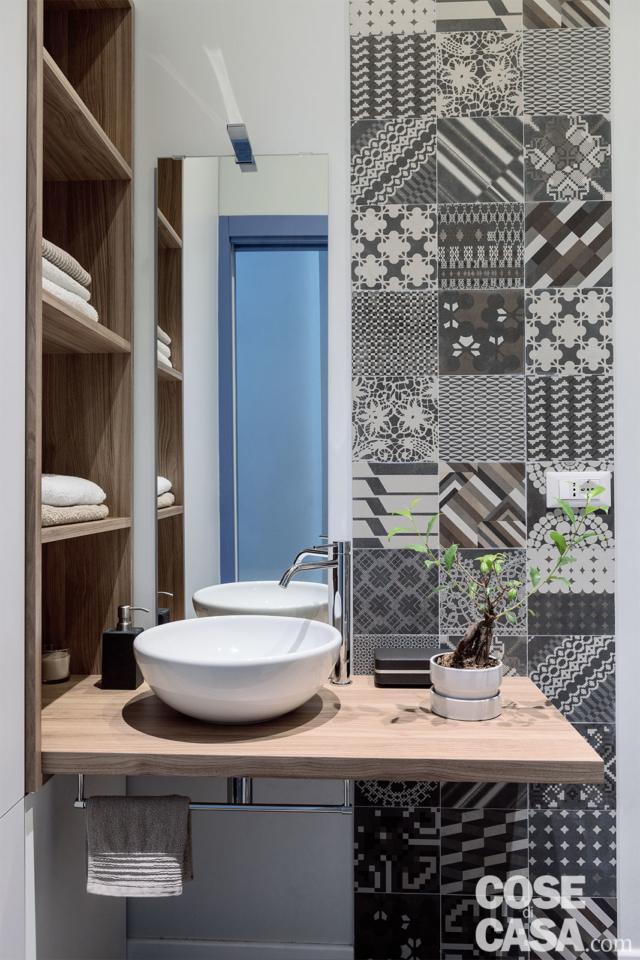 bagno con finiture decorative in gres con decori geometrici in chiaroscuro, lavabo da appoggio a catino, piano e nicchia in rovere, specchio