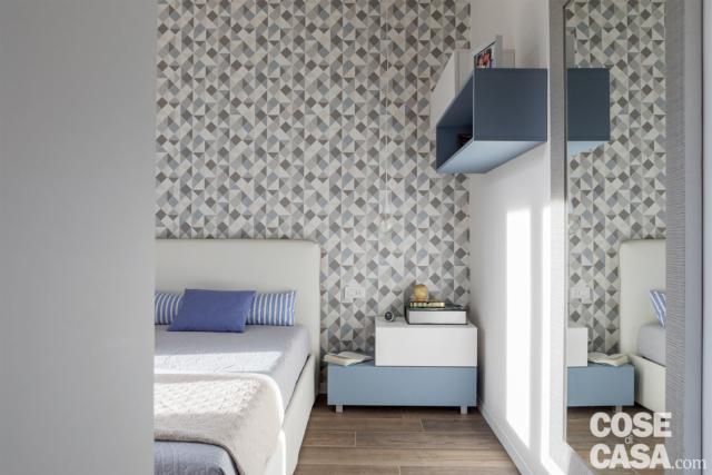 camera matrimoniale con letto tessile, parete di fondo rivestita in carata da parati a motivo geometrico sui toni del grigio. comodino in laccato bianco e azzurro, pavimento in gres effetto legno