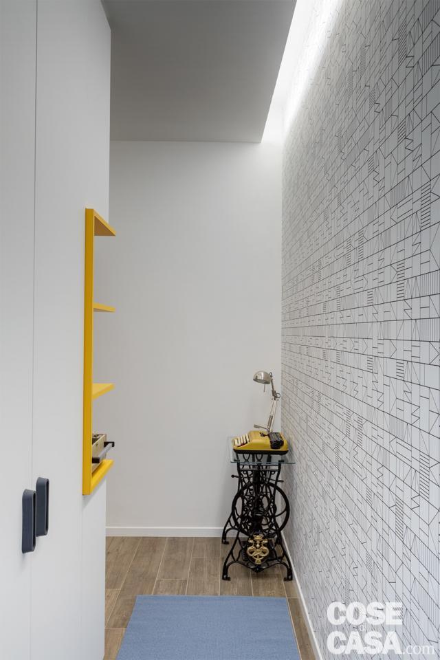 ingresso, armadiatura, parete rivestita con carta da parati, nicchia, taglio luminoso nel controsoffitto, base di un'antica macchina per cucire nell'angolo