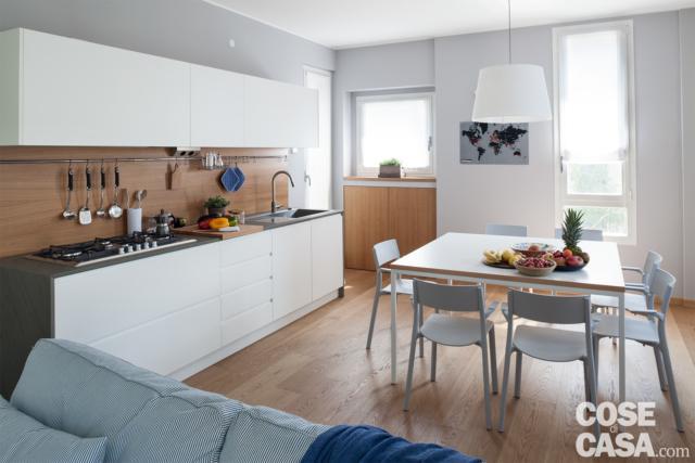 cucina in linea con zona cottura e lavaggio, finestre, zona pranzo con tavolo quadrato a otto posti a centro stanza