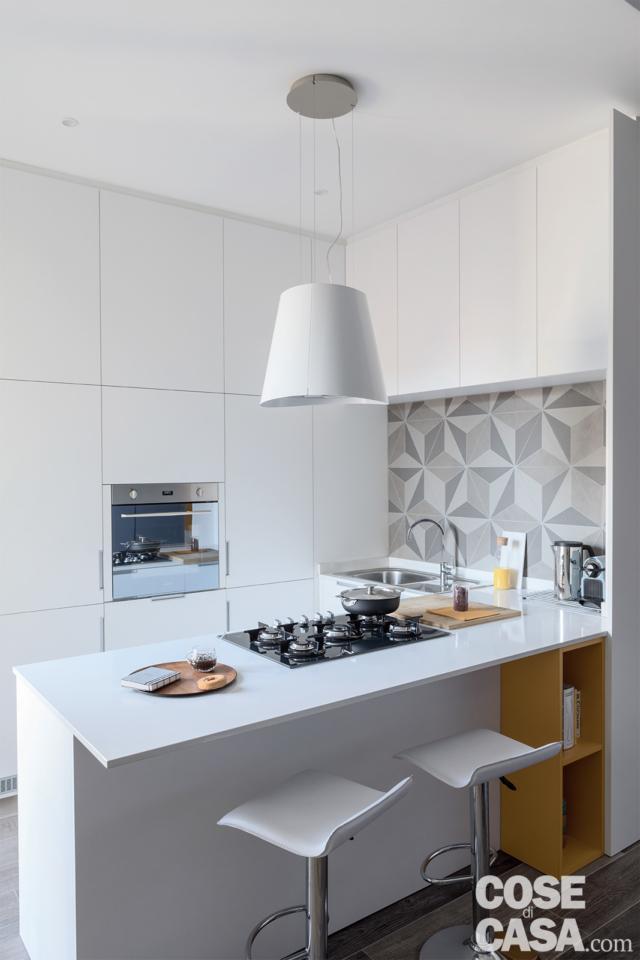penisola della cucina in laccato bianco con bancone snack e sgabelli da bar, zona cottura con piano a gas in acciaio inox e cappa d'arredo