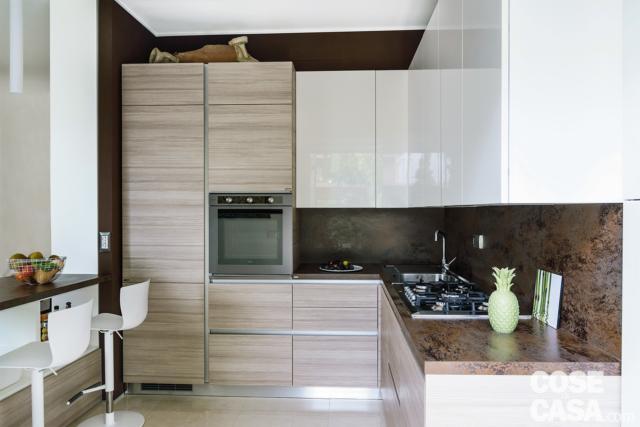 open space, cucina, composizione angolare, bancone snack, basi e pensili in legno e bianco laccato lucido