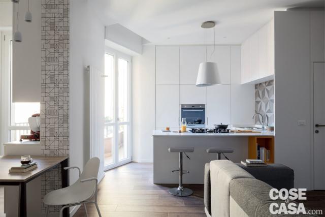 zona pranzo, cucina in laccato bianco con finiture decorative a parete, portafinestra affacciata sul balcone, pavimento in gres effetto legno