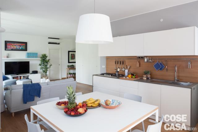 open space con soggiorno, zona pranzo con tavolo quadrato in laccato bianco, cucina a vista con alzata in rovere , zona cottura, lavello e pensili