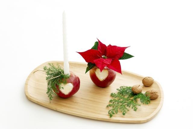 Inserire una candela in una delle mele, riempire la provetta nell'altra mela con dell'acqua e inserire una Stella di Natale recisa. Disporre tutto sul vassoio,aggiungendo altre decorazioni.