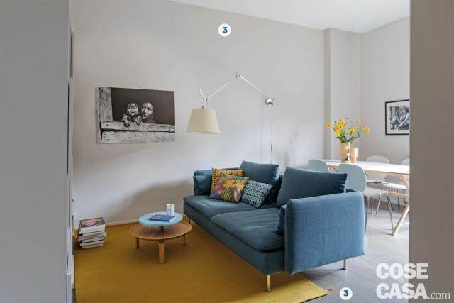 bilocale, zona conversazione, divano blu, lampada a bracco estensibile, tappeto giallo