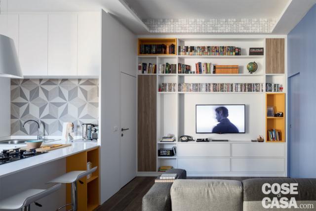 Parete attrezzata del soggiorno con vano tv, davanti al divano, con inserti in giallo e rovere, cucina con finiture decorative, porta filomuro della camera rifinita in bianco come il muro