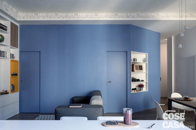 In soggiorno, parete smaltata in azzurro con le porte del bagno e dello studio rifinite nello stesso colore, divano, mobile a giorno, tavolo da pranzo. In primo piano penisola della cucina