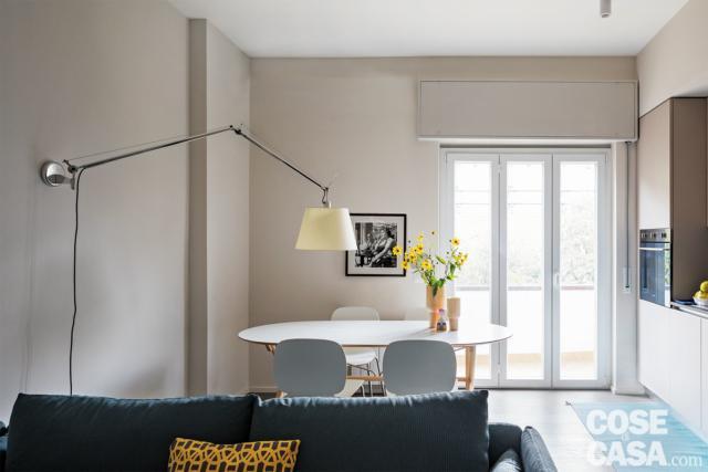 bilocale, zona pranzo, tavolo, sedie, applique a braccio estensibile, portafinestra, zona cottura