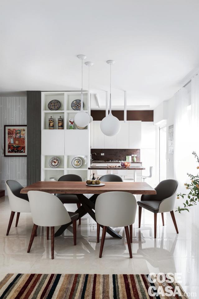 open space, zona pranzo, tavolo in legno di mogano, lampade a sospensione, pavimento in gres