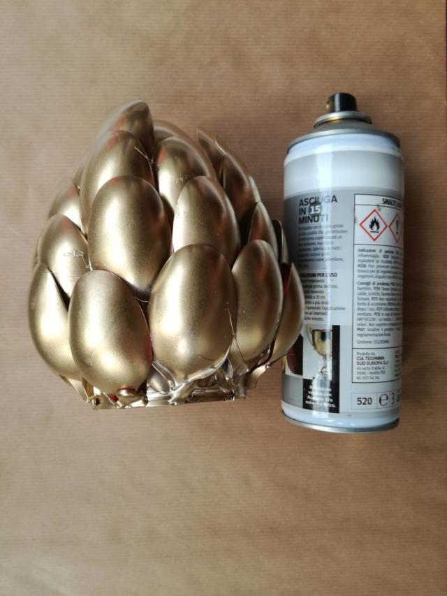 Decorate il vasetto con alcune velature di oro spray, stese in più tempi permettendo al colore di asciugarsi. Colorate anche la base e la parte interna del vasetto, quindi ripetete se necessario.