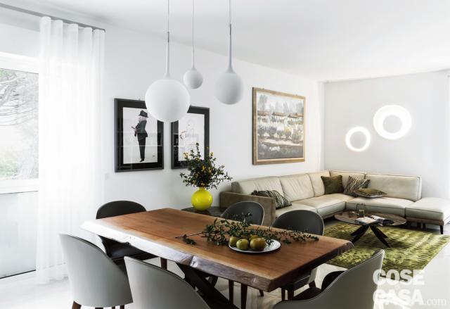 open space del living, zona conversazione, divano angolare in pelle, tavolo in legno, sedie, lampade a sospensione sferiche, portafinestra