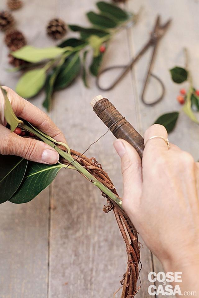 3. Tagliate le fronde di agrifoglio in rametti lunghi circa 20 cm ed eliminate le foglie alla base. Avviate il lavoro sulla ghirlanda fissando con il fil di ferro il primo rametto di agrifoglio e proseguite fino a coprire di foglie verdi e bacche rosse tutta la ghirlanda facile. Inserite regolarmente ogni 5-6 cm circa una pigna. Abbiate l'accortezza di sovrapporre i rami in modo da nascondere il fil di ferro.