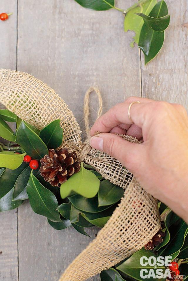 4. Con la corda, legate il pezzo di nastro di iuta nel mezzo e fate un anello per poter appendere la ghirlanda a un gancio.
