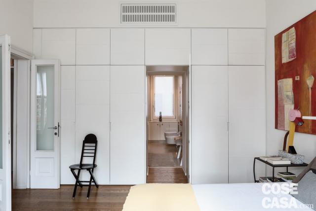 camera matrimoniale, armadio incassato in laccato bianco, passaggio verso il bagno a uso esclusivo, porta vetrata originale