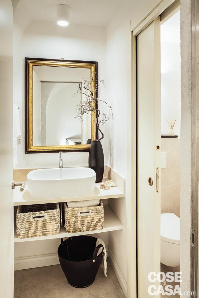 bagno, lavabo da appoggio, specchio vintage con cornice dorata, porta scorrevole a scomparsa, faretto
