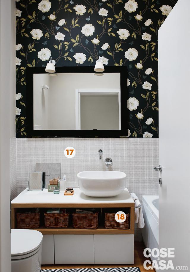 Bagno del mini loft ristrutturato, carata da parati decorativa su fondo scuro e disegni bianchi, lavabo da appoggio, specchio, sanitari e vasca