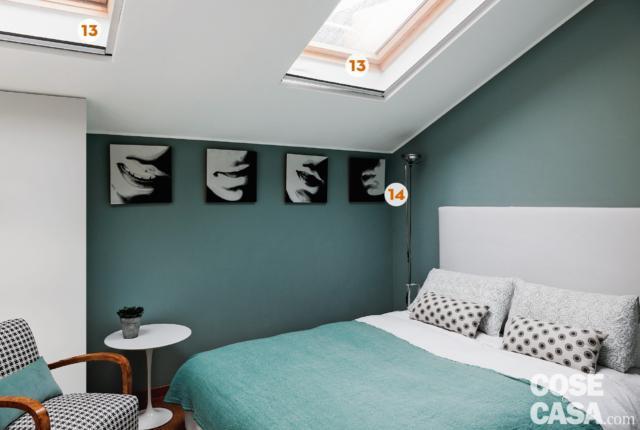 sottotetto, camera matrimoniale, pareti azzurre, lucernari, letto tessile, testiera imbottita, poltroncina di design