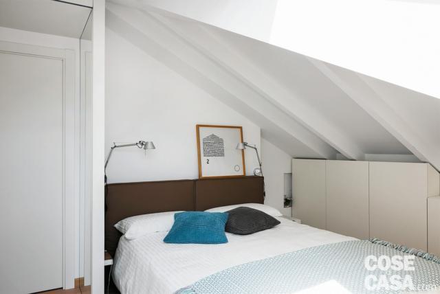 sottotetto ristrutturato, camera matrimoniale, letto, applique di design orientabili, mobile contenitore