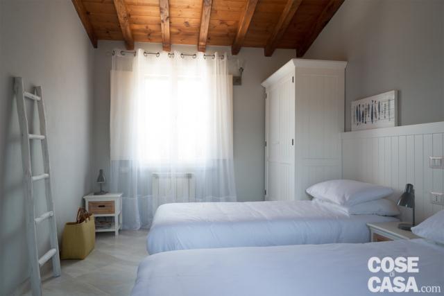 camera, due letti singoli, boiserie, armadio bianco, travi a vista in legno