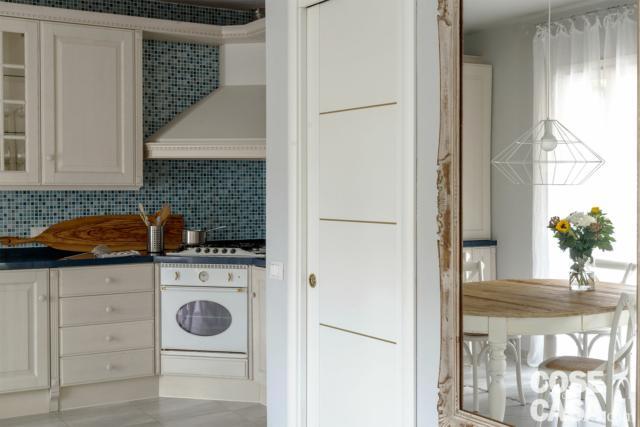 cucina tradizionale, rivestimento  a mosaico, pensili vetrati, tavolo da pranzo con piano in legno, sedie bianche