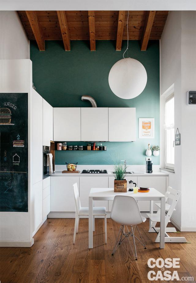 angolo cottura, composizione in laccato bianco, parete colorata, sospensione sferica, tavolo da pranzo, finestra