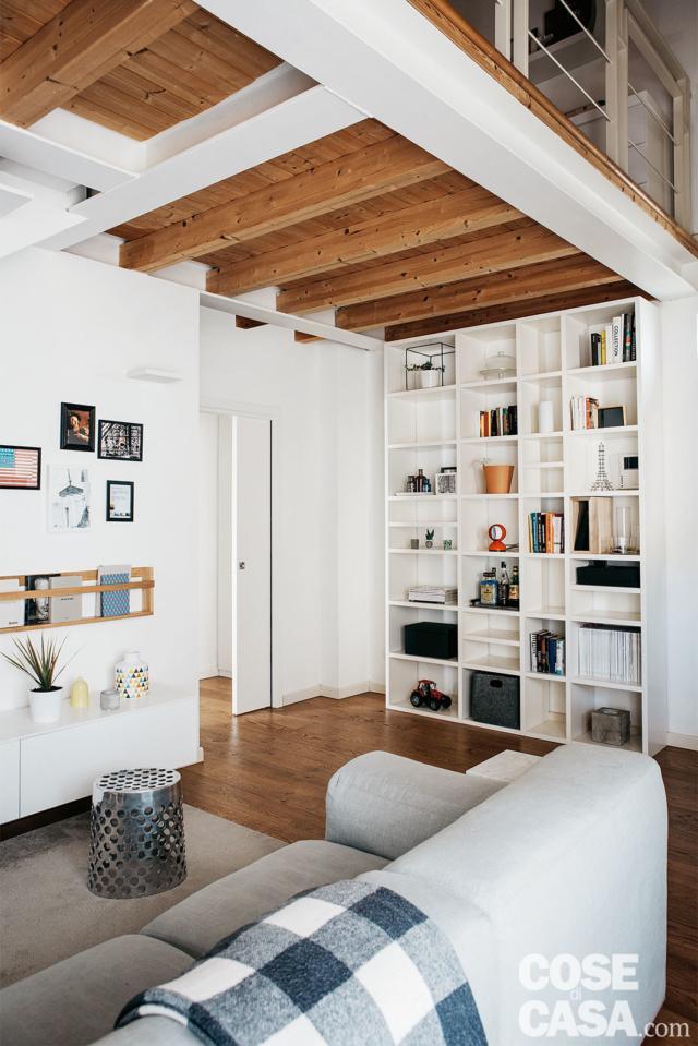 lliving, libreria a giorno in laccato bianco, travi a vista, divano, porta scorrevole a scomparsa