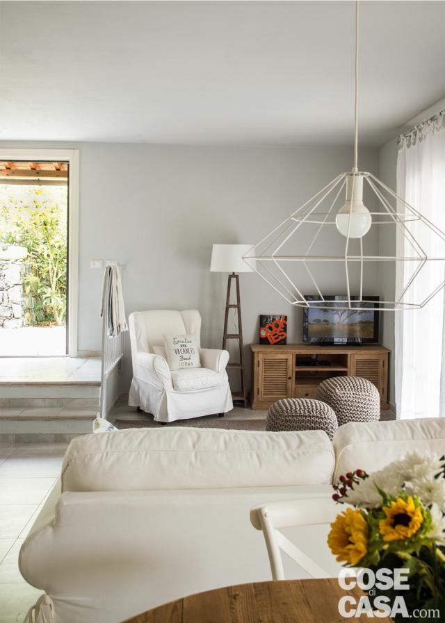 sottotetto su due livelli, ingresso, gradini zona conversazione, divano e poltrona bianchi, lampada a sospensione in metallo, lampada da terra