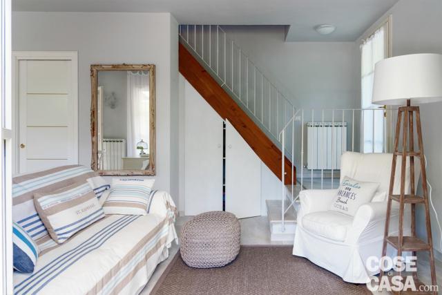 sottotetto su due livelli, scala, divano rigato, pouf, poltrona, lampada da terra, specchio rétro, porta scorrevole