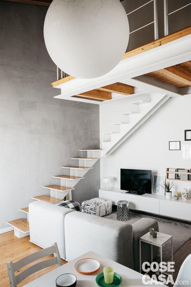 scala in ferro e legno, zona conversazione, divano bianco, zona tv con mobile basso