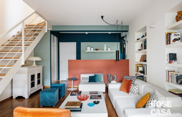 Zona conversazione con divano bianco e poltrona, pouf turchesi e muretto divisorio color corallo, librerie, scala