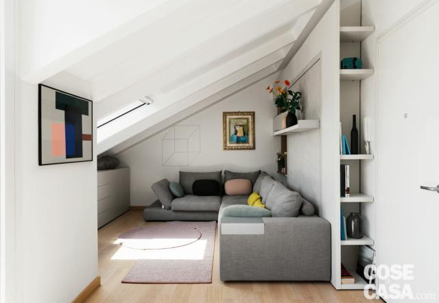 sottotetto ristrutturato, zona conversazione, tetto a spiovente, lucernario, divano angolare, colonna portaoggetti