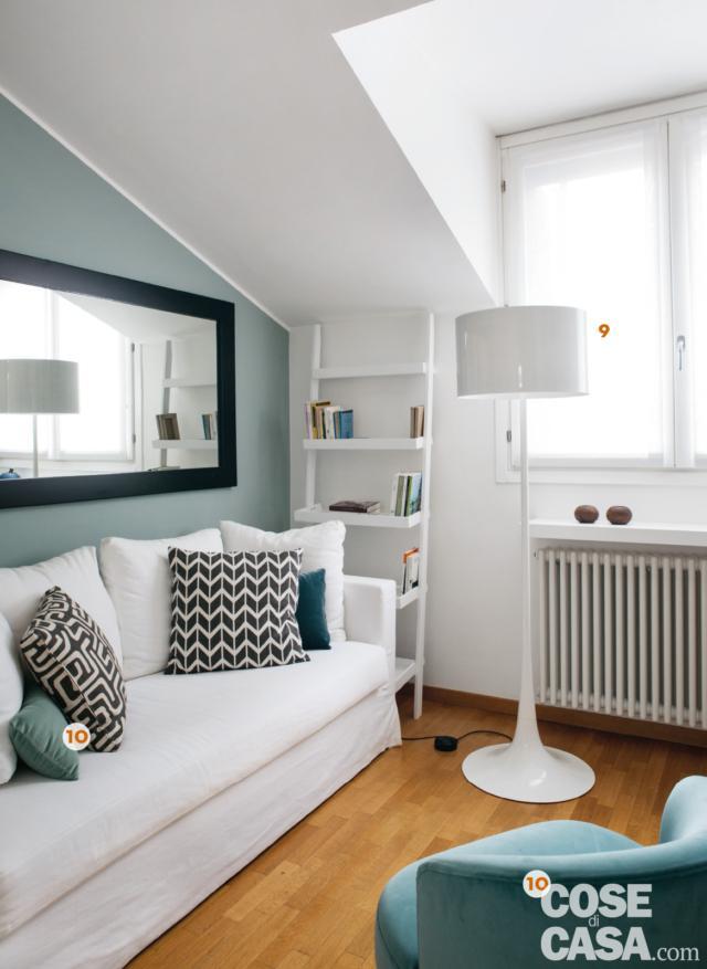 sottotetto del mini loft ristrutturato, parete azzurra, divano, poltroncina, lampada da terra di design, mini libreria