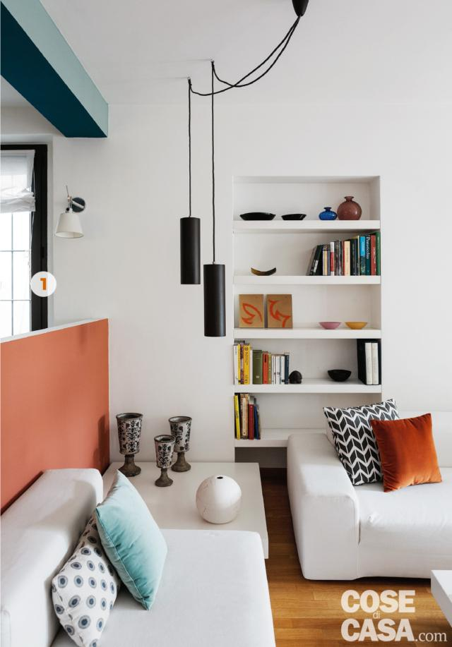 zona conversazione dettaglio con tavolino nell'angolo e lampade  a sospensione cilindriche, libreria in nicchia