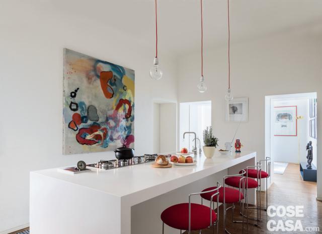 cucina, isola multifunzione, zona cottura, bancone snack, sospensioni a bulbo, doppio passaggio verso il soggiorno