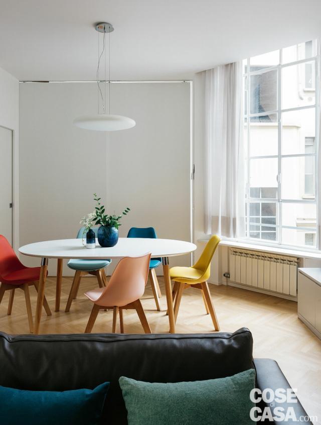 zona giorno, tavolo da pranzo, sedie colorate, pavimento in parquet, finestra, lampada a sospensione, divano