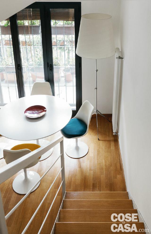 Scala, pavimento in parquet, zona pranzo, tavolo e sedie di design, lampada da terra, vetrata