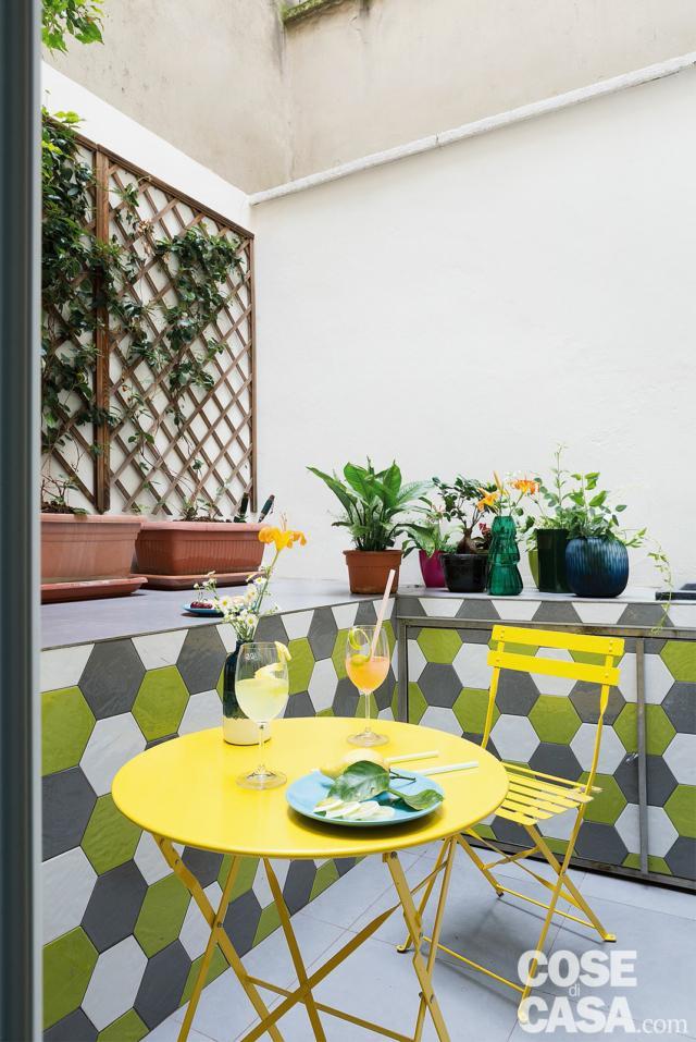 patio, zona pranzo con tavolino e sedie pieghevoli, muretto, rivestimento con piastrelle esagonali bianche verdi e grigie, graticcio per i rampicanti