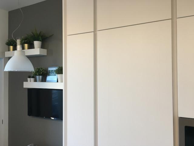 cucina bianca con gole verticali nelle armadiature a colonna